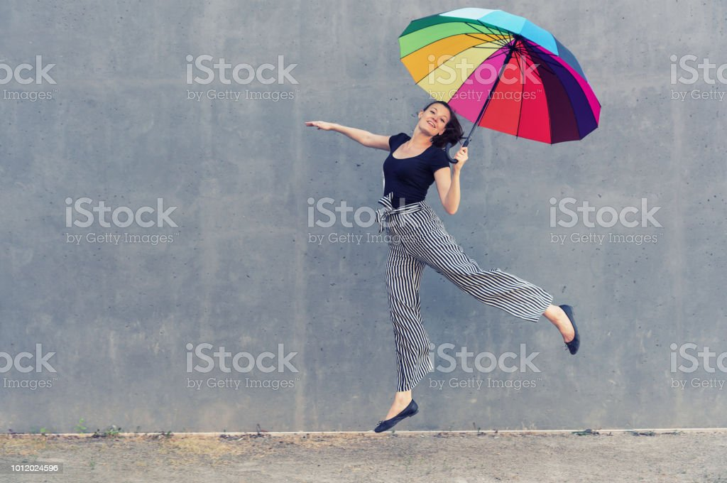 Young jumping woman with multicolored umbrella in front of a concrete...