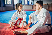 One young woman and one young man, karate students, resting on exercise mat after training.