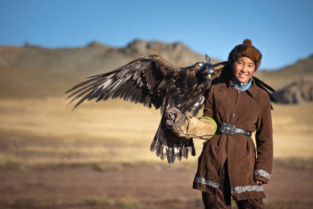 Young kazakh eagle hunter with his golden eagle. Traditional kazakh eagle hunter girl with his golden eagle that is used to hunt for fox and rabbit fur. Ulgii, Western Mongolia. kazakhstan stock pictures, royalty-free photos & images