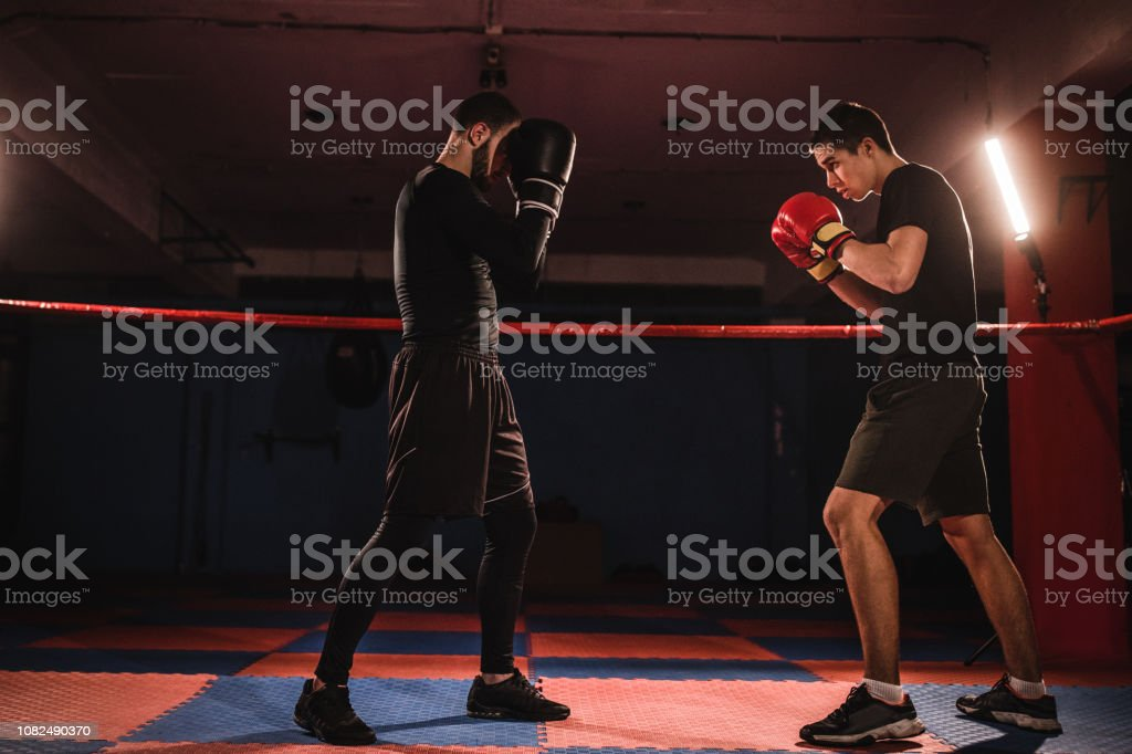 Two young male kick boxers fighting in boxing ring