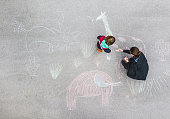 Young kid and his mother drawing on asphalt with chalk