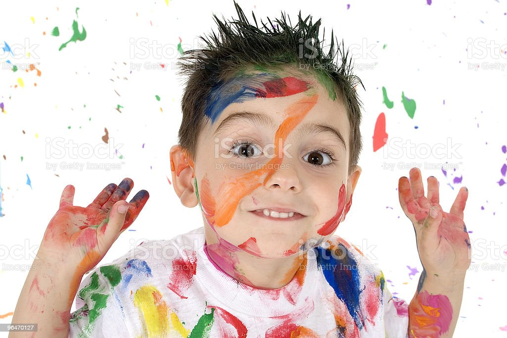 Young kid covered in paint raising his hands and smiling royalty-free stock photo