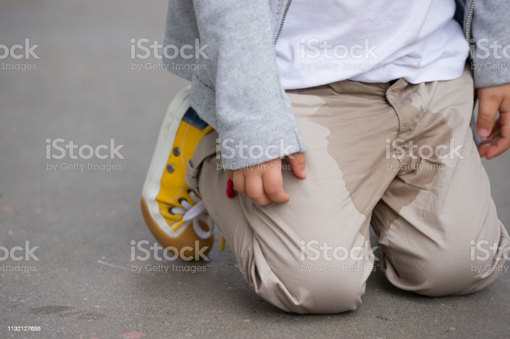 A young kid peeing on his pants on the street - Bed-wetting concept. Child pee on clothes. stock photo