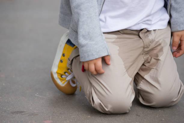 um miúdo novo que faz xixi em suas calças na rua-cama-conceito molhando. xixi da criança na roupa. - calça comprida - fotografias e filmes do acervo