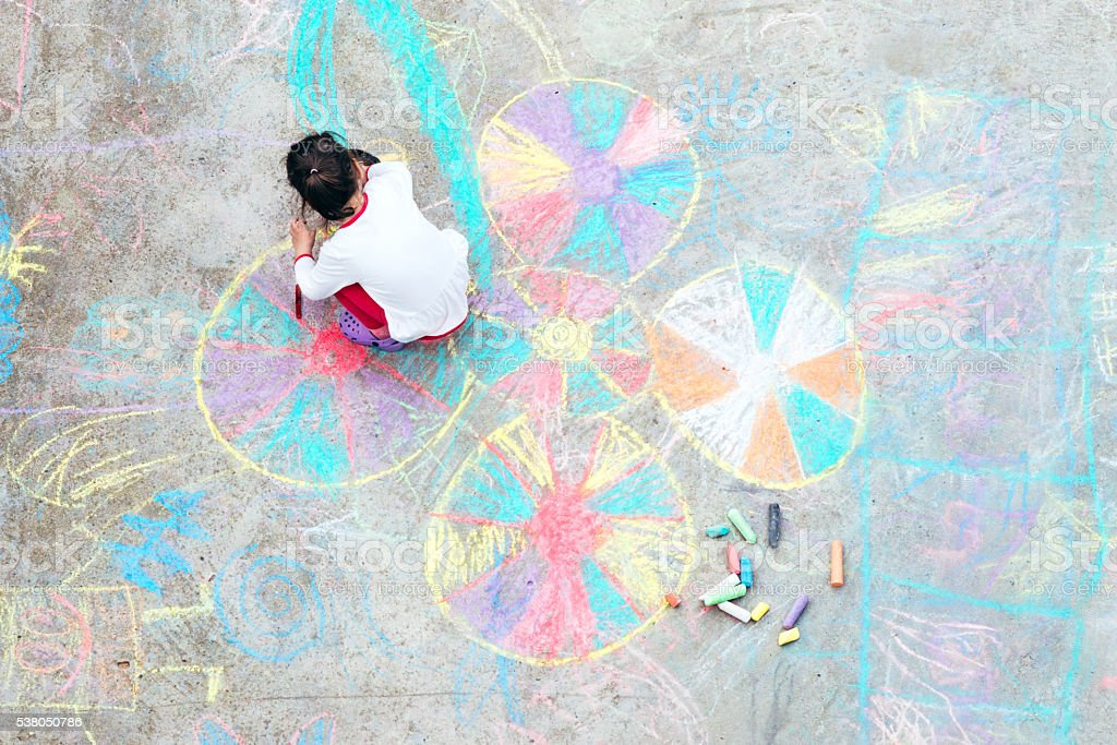 Young kid playing with chalk. stock photo