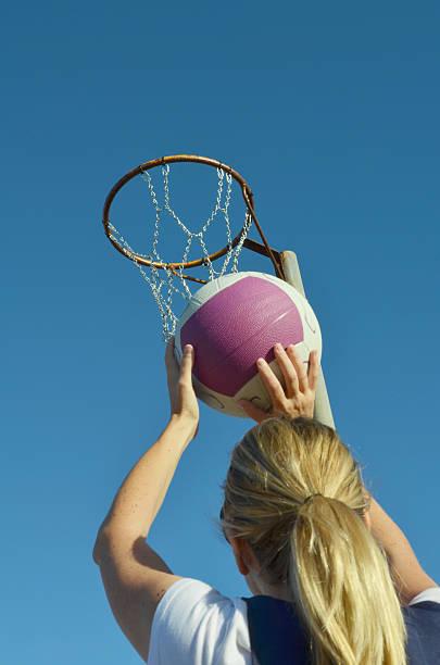 young kid shooting a basketball into a netball - netball stockfoto's en -beelden