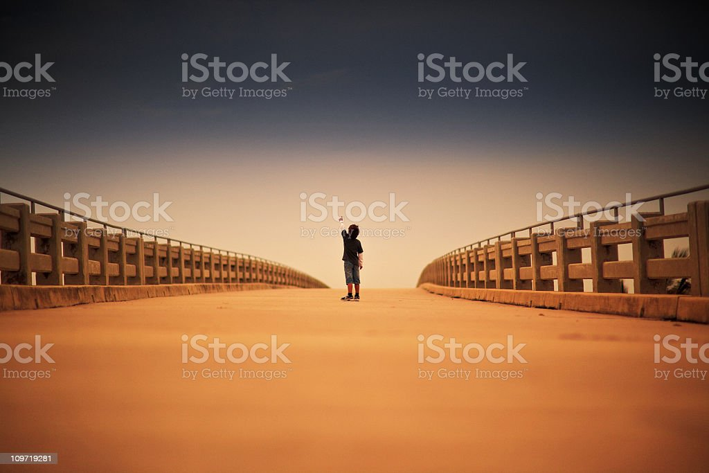 young kid signaling up standing in a lonely bridge royalty-free stock photo