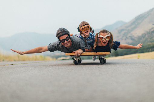 Two young children, a boy and a girl, are imagining flying into the sky while riding on a press cart with their father. They have their arms spread out like wings and ready to use imagination in being like an airplane and piloting the airplane into the sky. They love spending time together as a family. They are wearing flying goggles on a rural road in Utah, USA.