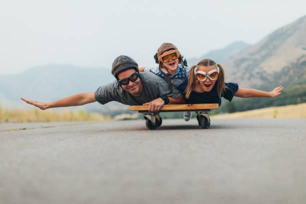 Kleine Kinder und Papa fliegen auf einem Presse-Wagen – Foto
