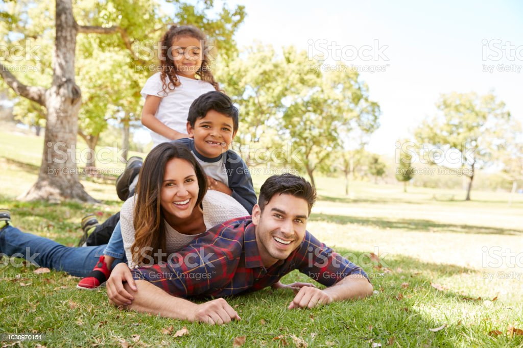 Young kids and parents lying in pile on the grass, portrait royalty-free stock photo