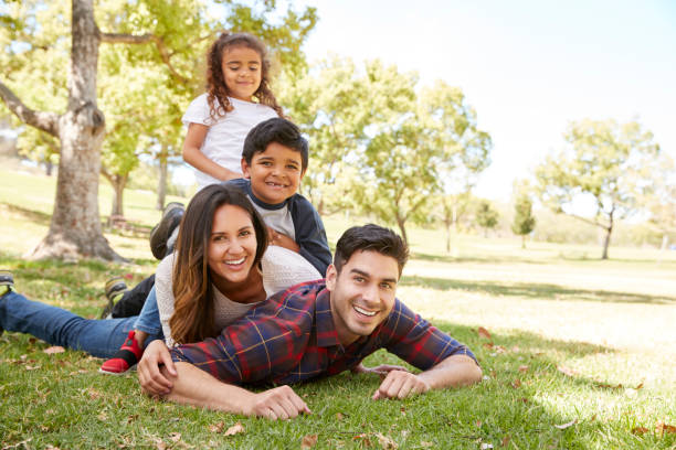 Young kids and parents lying in pile on the grass, portrait stock photo