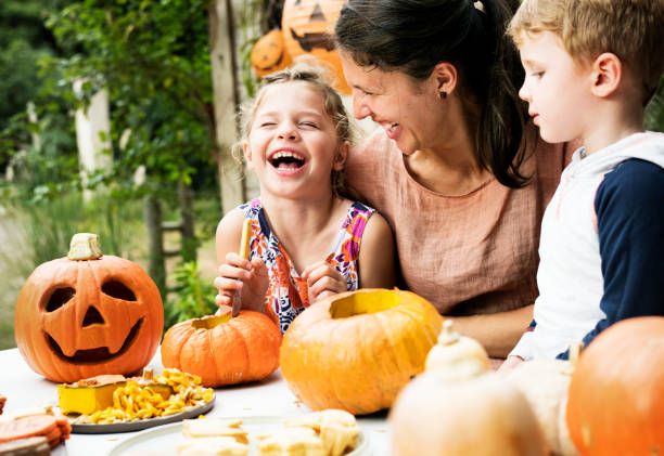 Young kids carving Halloween jack-o'-lanterns Young kids carving Halloween jack-o'-lanterns carving craft product stock pictures, royalty-free photos & images