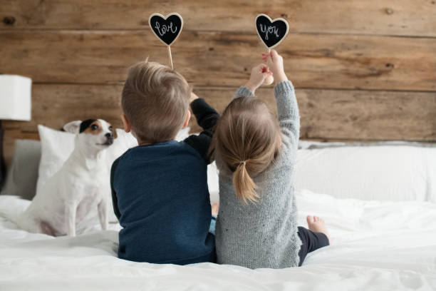 Young kids happy childrens family playing in the parent's bed with their for Young kids happy childrens family playing in the parent's bed with their Jack Russell dog. They hold in their hands a shape heart in chalk board. The photo can be use for Valentine's day, Mother's day, Father's day or birthday. The sweet little girl is 20 months and the cute little boy is 4 years old. Photos was taken in  Quebec Canada. girl bedroom stock pictures, royalty-free photos & images