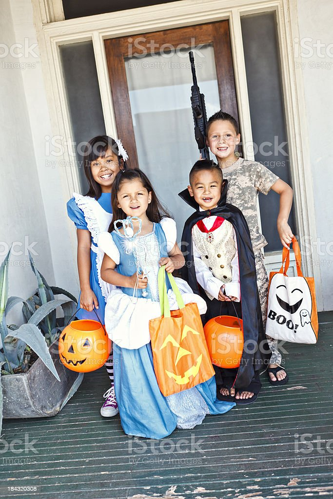 Young kids standing infront of a door trick or treating royalty-free stock photo