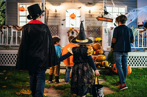 Young kids trick or treating at night during Halloween