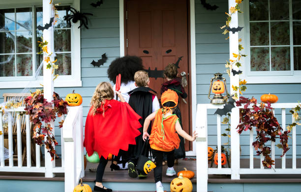 Young kids trick or treating during Halloween Young kids trick or treating during Halloween trick or treat stock pictures, royalty-free photos & images
