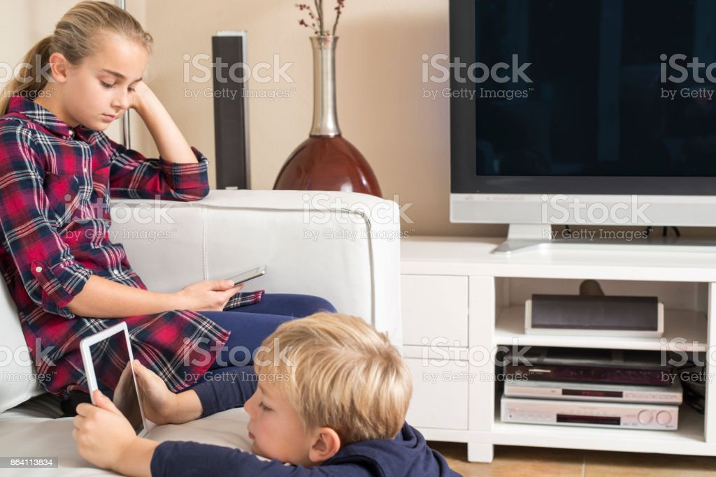 young kids using tablet and mobile in living room stock photo