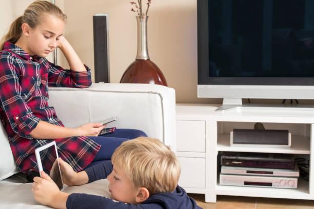 young kids using tablet and mobile in living room - tv e familia e ecrã imagens e fotografias de stock