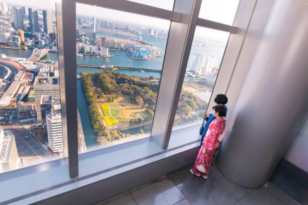 展望台から窓の外を見て若い着物カップル - 観測所 ストックフォトと画像