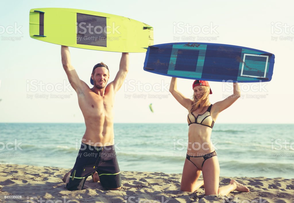 Young kitesurfers couple on the beach stock photo