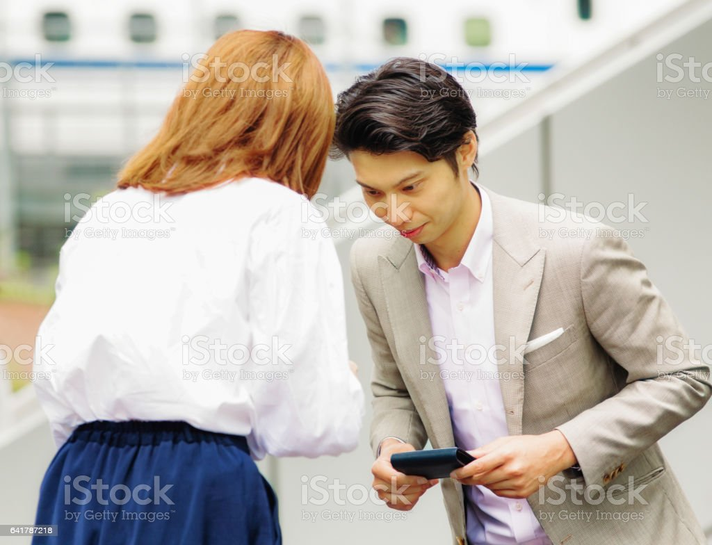 Young Korean worker bows to female Japanese colleague stock photo