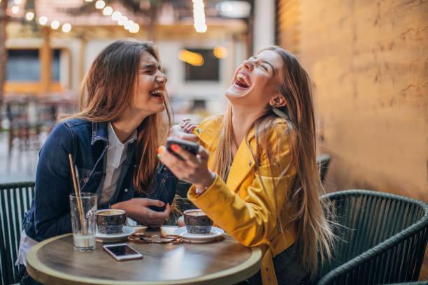 junge damen klatschen im café - freundin stock-fotos und bilder