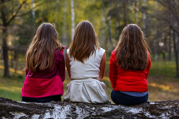 Young ladies sitting on tree trunk in the forest stock photo