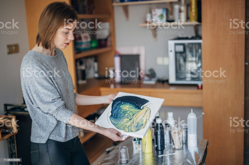 One woman, young lady artist, painting aquarelle picture in artist...