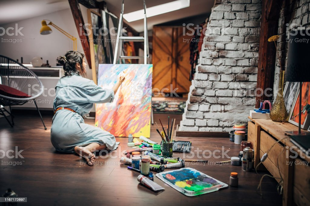 One woman, beautiful lady artist, painting on the floor in home...
