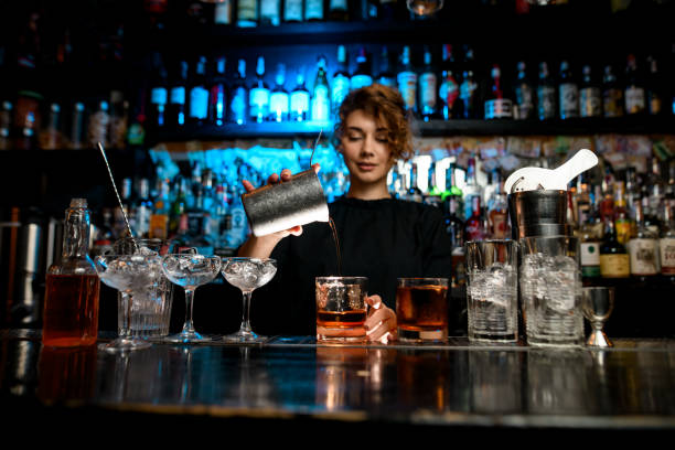 Young lady at bar pours cocktail into glass. Young lady at bar pours cocktail into glass. Different bar equipment stand on bar counter. bartender stock pictures, royalty-free photos & images
