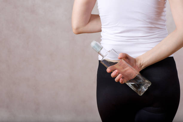 Young lady between 30 and 40 years old hides a bottle of vodka behind her back. stock photo