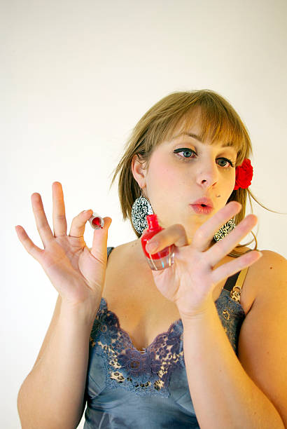 young lady blowing on freshly painted finger nails - mikefahl stock pictures, royalty-free photos & images