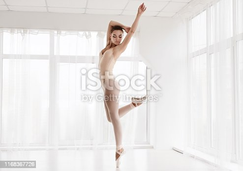 Professional Ballet Girl Dancing On Tiptoe In White Studio. Empty Space For Text