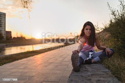 Young lady exercise near river at sunset
