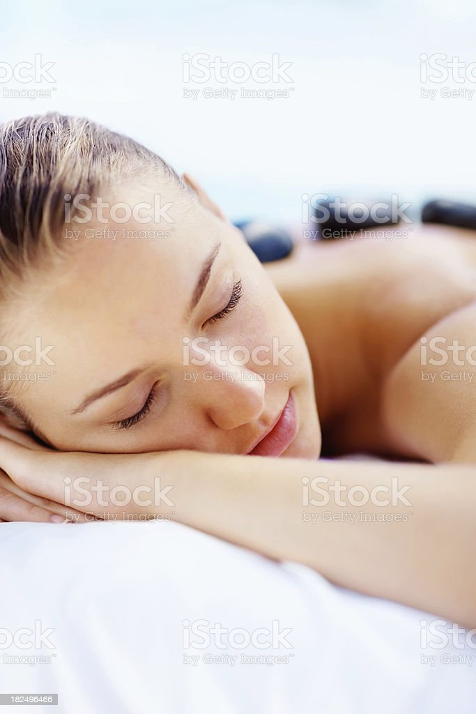 Young lady getting a stone massage at health spa royalty-free stock photo