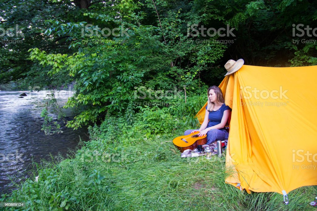 Young lady hiker sit near the tent .Traveling, freedom and active lifestyle concept - Royalty-free Activity Stock Photo