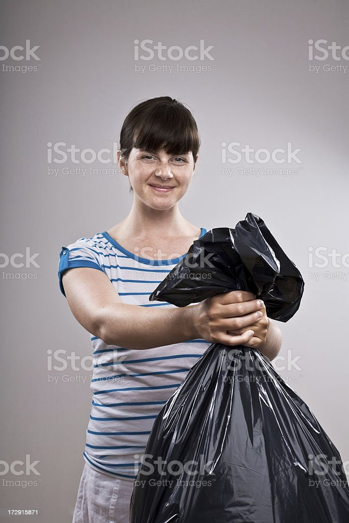 Young lady holding a big black plastic bag royalty-free stock photo