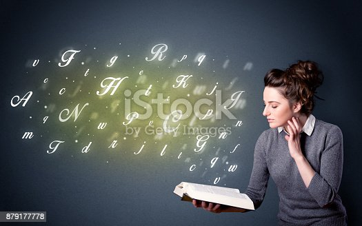 istock Young lady holding book with letters 879177778