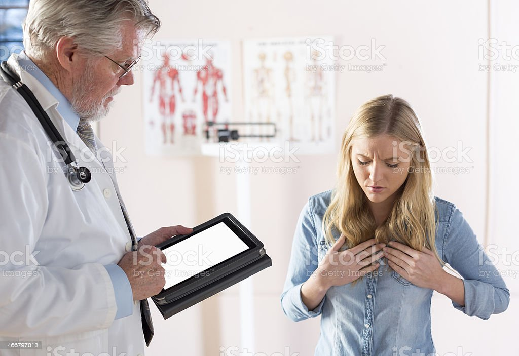 Young lady holding her chest with a doctor stock photo