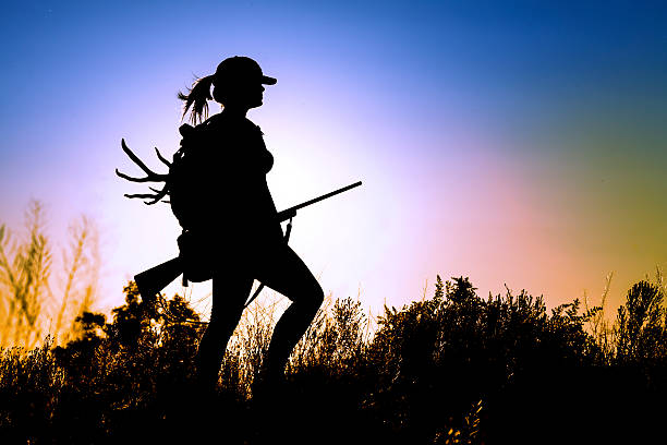 Young Lady Hunter young Lady on a Deer Hunt at sun sunset hunter stock pictures, royalty-free photos & images