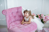 A young lady in a room with candles is having fun and smiling on a pink upholstered chair.