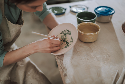 Young lady in apron painting ceramic plate at workshop