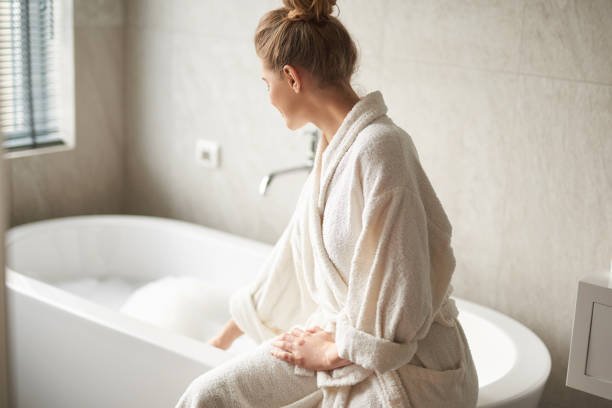 Young lady in bathrobe ready taking bath stock photo
