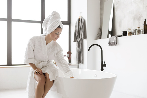 Young lady in bathrobe touching water