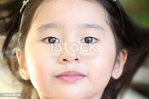 A Chinese ethnicity young girl is feeling cheerful at home.