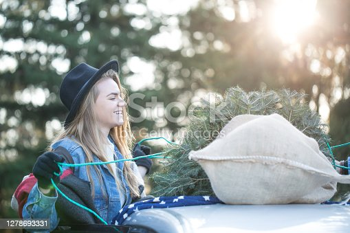 Young lady in shopping for Xmass tree, preparing for transportation