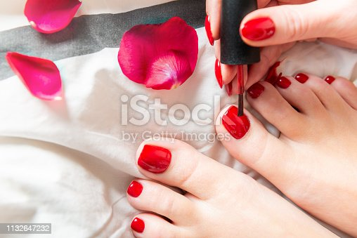 istock Young lady is applying red polish on toes 1132647232