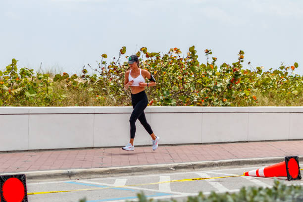 Young lady jogging Ft. Lauderdale Beach boardwalk stock photo