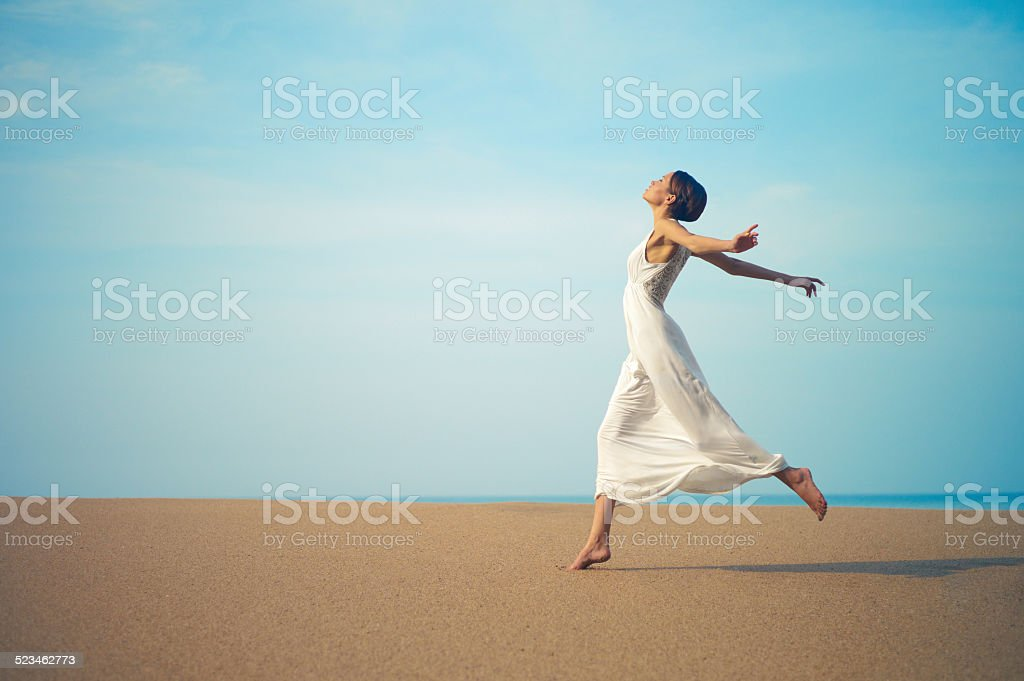 Young lady jumping on the beach stock photo