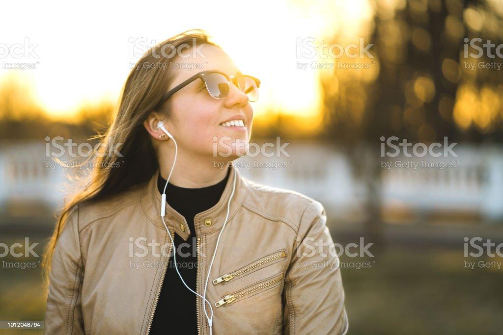 Jovem ouvindo música com fones de ouvido brancos pequenos. Mulher sorridente feliz ouvir audiobook do lado de fora. Gostar da vida na natureza. - foto de acervo